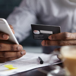Man holds credit card and phone while online shopping.
