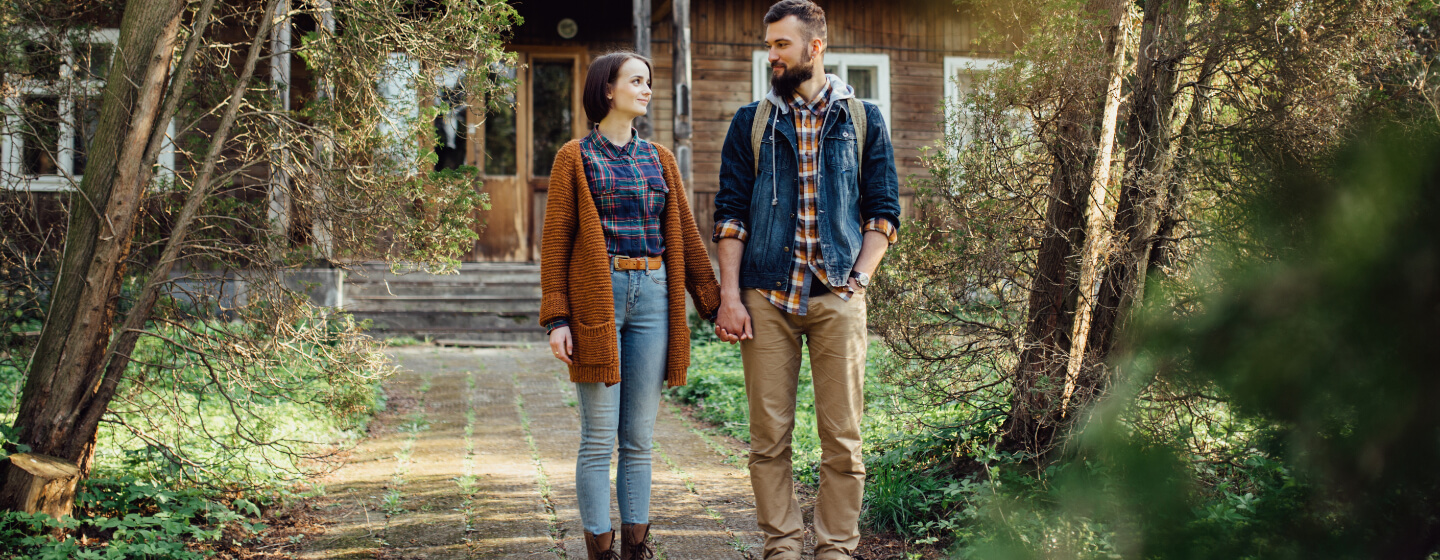 Young couple hold hands in front of house.